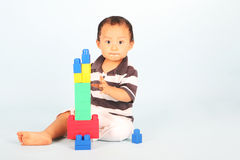 Toddler plays block. Cute toddler playing with his blocks shot over blue background Royalty Free Stock Photo