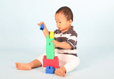 Toddler plays block. Cute toddler playing with his blocks shot over blue background Royalty Free Stock Images