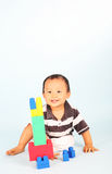 Toddler plays block. Cute toddler playing with his blocks shot over blue background Stock Images