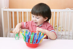 Toddler plays with clothes pins Royalty Free Stock Images