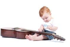 Toddler plays guitar Stock Photography