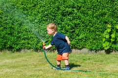 Toddler plays with a hose Royalty Free Stock Images