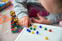 Toddler plays with pins Royalty Free Stock Photo