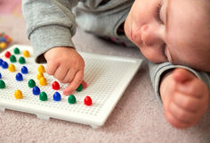 Toddler plays with pins Royalty Free Stock Photos