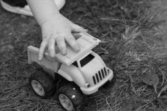 Toddler plays with truck outdoors Royalty Free Stock Images
