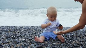 Newborn baby boy plays at the windy seaside with stones. Toddler plays at the windy seaside stock footage