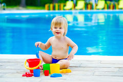 Toddler by the pool palying with toy bucket set Royalty Free Stock Images