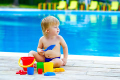 Toddler by the pool palying with toy bucket set Royalty Free Stock Photography