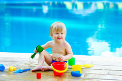 Toddler by the pool with toy bucket set Royalty Free Stock Photos