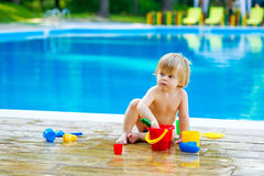 Toddler by the pool with toy bucket set Royalty Free Stock Images