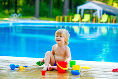 Toddler by the pool with toy bucket set Stock Photos