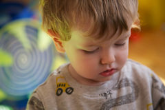 Toddler portrait. Portrait of young blond toddler intent on playing stock photo