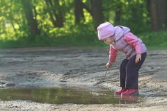 Toddler preschooler exploring summer puddle wearing red gums thin tree twig in hand Stock Photography