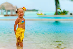 Toddler pretty girl in bikini standing on tropical Stock Photos