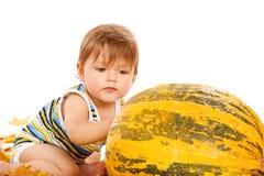 Toddler with pumpkin Stock Photos