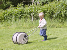 Toddler pushing water barrel Stock Photos