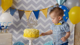 A toddler puts a finger inside a birthday cake. stock video