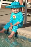 Toddler putting her feet in a swimming pool.