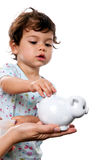 Toddler putting money in piggy bank Stock Photography