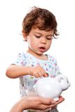 Toddler putting money in piggy bank Royalty Free Stock Image