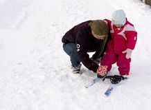 Toddler putting on skis. Mother helping toddler to put on ski Royalty Free Stock Images
