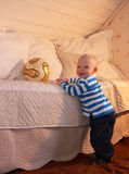 Toddler reaching for a Ball. A toddler reaching for afootballl on a bed Stock Image