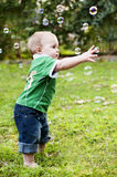 Toddler reaching for soap bubbles. Little boy toddler reaching and popping soap bubbles in the bard garden during a birthday party Royalty Free Stock Photography