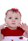 Toddler with Red Hair Bow. Toddler with bright blue eyes, wearing a red top and red hair bow, with her fingers touching her face Stock Image