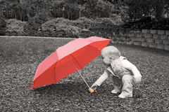 Toddler with red umbrella. Small caucasian toddler stooping to pick up a red umbrella, sepia with selective coloring royalty free stock photo