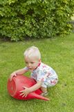 Toddler with red watering can Stock Image