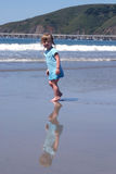 Toddler and reflection on Beach. Toddler girl walking on the beach, nice reflection on the wet sand Royalty Free Stock Photos