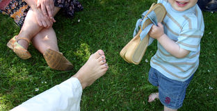 Toddler removing woman shoe. High angle view of playful toddler removing woman's shoe outdoors Royalty Free Stock Photo