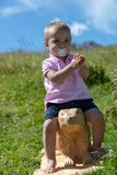 Toddler riding on a groundhog. Hand clapping toddler enjoying the sunshine and fresh air while riding on a wooden groundhog near Seiser Alm, South Tyrol, Italy royalty free stock photography