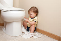 Toddler ripping up toilet paper Royalty Free Stock Images
