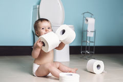 Toddler ripping up toilet paper in bathroom Royalty Free Stock Photo