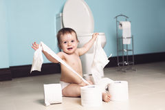 Toddler ripping up toilet paper in bathroom Royalty Free Stock Images