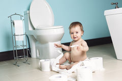 Toddler ripping up toilet paper in bathroom Stock Photos