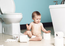 Toddler ripping up toilet paper in bathroom Stock Photography