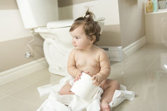 Toddler ripping up toilet paper in bathroom Royalty Free Stock Image