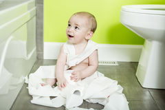 Toddler ripping up toilet paper in bathroom. A Toddler ripping up toilet paper in bathroom Royalty Free Stock Image