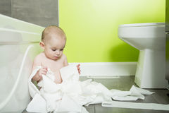 Toddler ripping up toilet paper in bathroom Stock Image