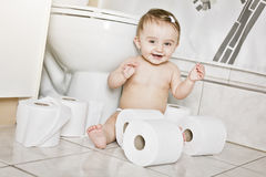 Toddler ripping up toilet paper in bathroom. A Toddler ripping up toilet paper in bathroom Stock Photo