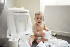 Toddler ripping up toilet paper in bathroom Stock Images