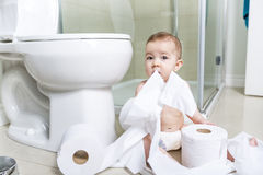 Toddler ripping up toilet paper in bathroom Royalty Free Stock Photography