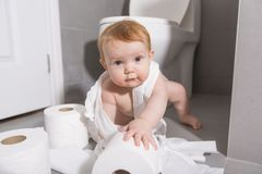 Toddler ripping up toilet paper in bathroom. A Toddler ripping up toilet paper in bathroom Stock Photos