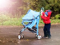 Toddler rolls stroller himself outdoors Royalty Free Stock Photos