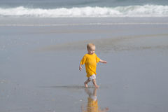 Toddler running on beach at low tide Stock Photo