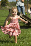 Toddler running outdoors Stock Photo