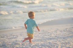 Toddler running on sand on the beach near the ocean Stock Photos