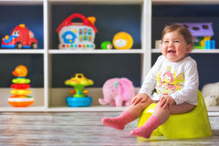 Toddler`s first days on the potty. Happy female toddler sitting on the potty, inside her room Royalty Free Stock Photography